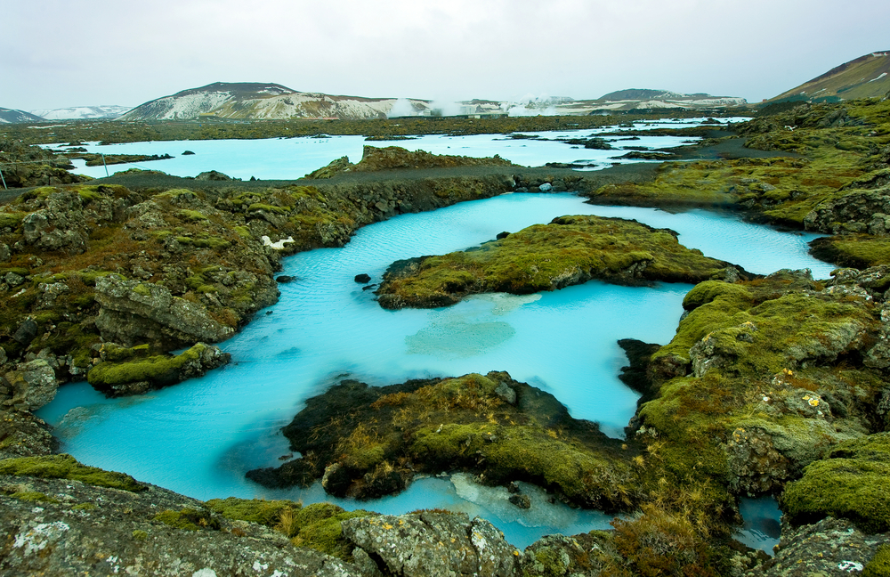 The blue water between the lava stones covered with moss just outside The Blue Lagoon Resort
