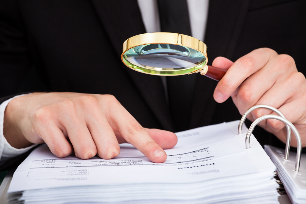 An image of businessman looking at document through magnifying glass.