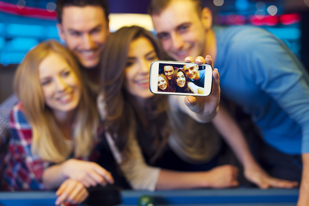 An image of smiling friends taking selfie photo from nightclub with billiard.
