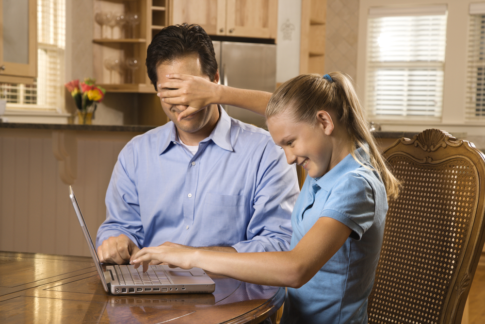 An image of young girl working on laptop at home covering man's face with hand.