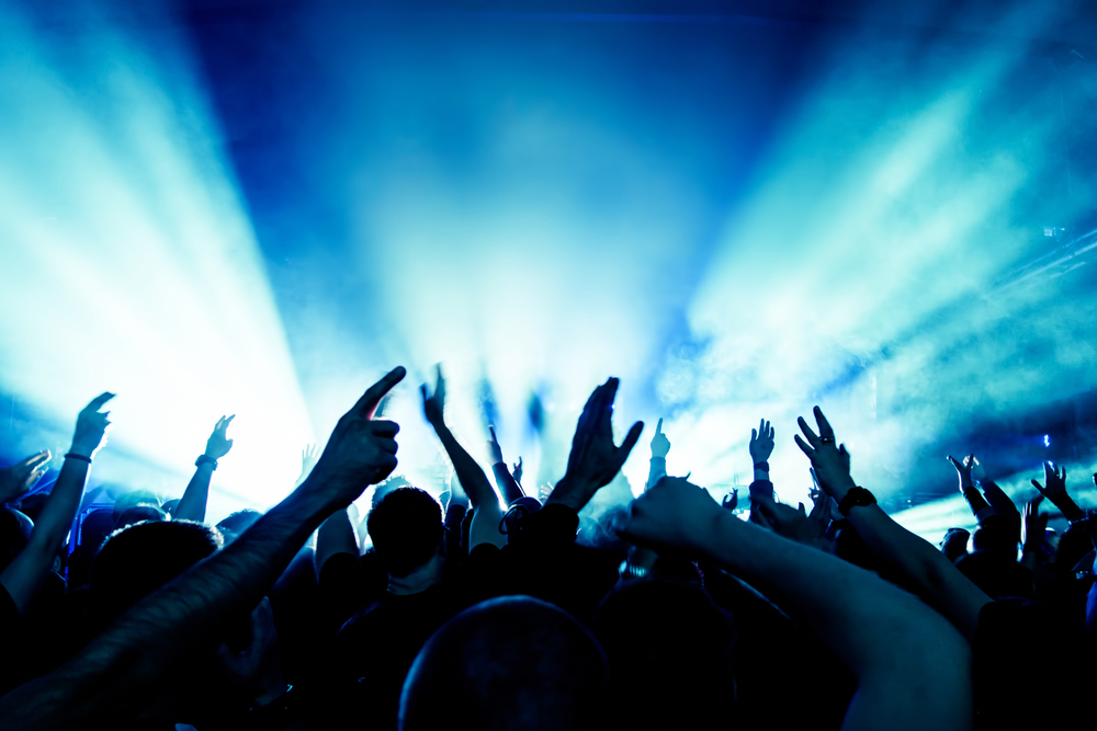 A cheering crowd in front of a stage at a music event